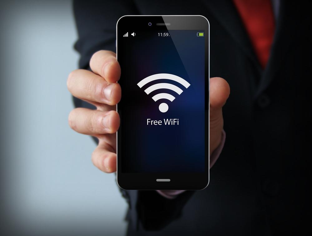 Biznes-i-kommunikatsionnoe-ponyatie-podvizhnosti-biznesmen-derzhashhiy-sovremennyiy-smartfon-simvolom-zonyi-besplatnogo-Wi-Fi