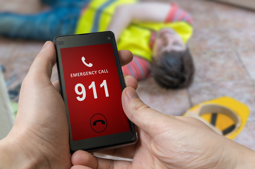 Man dialing emergency 911 number on smartphone.