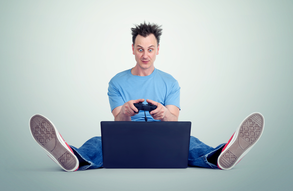 Funny man with a joystick sits on the floor in front of a laptop Gamer plays