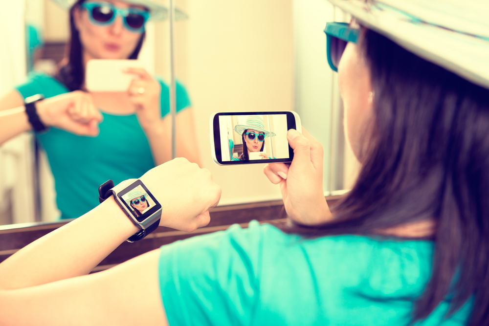 Woman taking self portrait selfie photo and sends it to smartwatch
