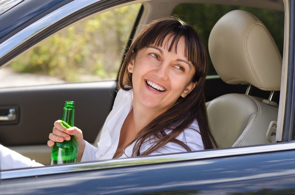Drunk woman driving laughing out of the side window as she sits behind the steering wheel clutching her bottle of booze