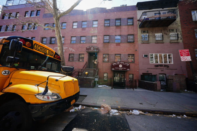 Photograph of a school bus in front of a 3-story brick building.